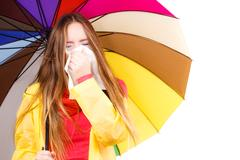Woman under umbrella sneezing in tissue Stock Photos
