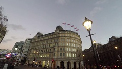 4K COLLECTION OF BRITISH FLAGS IN  STRAND TRAFALGAR SQAURE AT SUNSET LAMP POST Stock Footage