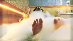 Beautiful brunette woman taking foamy bath and playing with foam Stock Footage