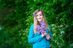 Beautiful young woman with a bouquet of lilacs in hands Spring Garden Stock Photos