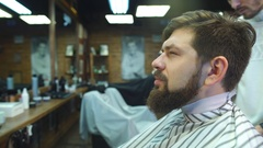 Confident man visiting hairstylist in barber shop Stock Footage