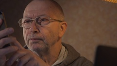 Older man using a laptop and talking on the phone Stock Footage