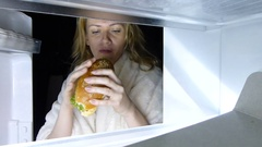 Woman opens the refrigerator at night. bulimia, sandwich, pastry Stock Footage
