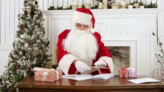 Santa Claus sorting out paper letters from children Stock Footage