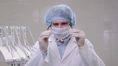 Man doctor surgeon in a mask and cap stands in an operating room in dental Stock Footage