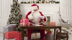 Santa Claus checking his list of presents Stock Footage