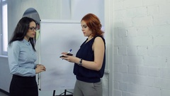 Manager explains to new employee how to draw graphs inside office Stock Footage