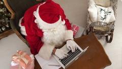 Busy Santa Claus preparing presents using laptop Stock Footage