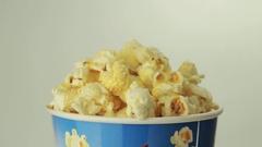 Salty popcorn slowly rotates on white background Stock Footage