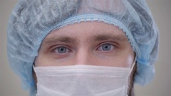 Handsome surgeon in mask is looking at camera, standing in a modern operating Stock Footage
