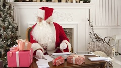 Busy Santa sorting chidlren's letters while cute little helper bringing him a Stock Footage