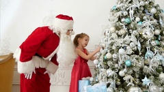 Santa Claus helping pretty little girl to decorate Christmas tree Stock Footage
