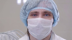 Portrait of doctor in mask and white uniform wearing glasses in modern hospital Stock Footage