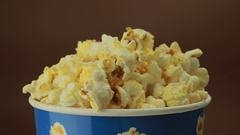 Salty popcorn slowly rotates on brown background Stock Footage