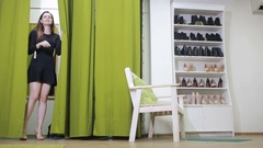 Happy pretty young woman trying on clothes in dressing room of clothing shop Stock Footage