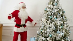 Santa Claus doing funny robot dance next to the Christmas tree Stock Footage