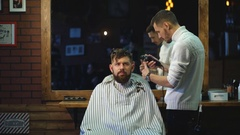 Close-up of hairdresser checking symmetry of haircut of his client at barbershop Stock Footage