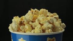Salty popcorn slowly rotates on black background Stock Footage