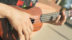 Young teenager playing an acoustic guitar outdoors Stock Footage