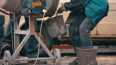 Concrete Mixer Builders and People Working at a Construction Site. Slow Motion Stock Footage