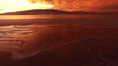 Flying backwards from ice on lake to higher aerial view of colorful sunset Stock Footage