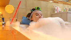Beautiful brunette woman wearing cosmetic face mask relaxes in foamy bath Stock Footage