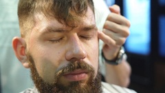 Male barber in plaid shirt combing hair of a male client at barbershop Stock Footage