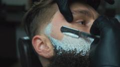 Barber cutting bearded brutal man, barber shop salon Stock Footage