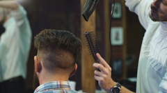 Unequaled barber is drying the hair of his client hair cape in the barbershop Stock Footage