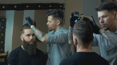 New hairstyle. Side view of young bearded man getting groomed at hairdresser Stock Footage