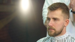Cheerful skillful barber making a haircut with scissors to a young bearded man Stock Footage