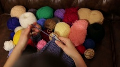A young girl knits a scarf crochet. Stock Footage