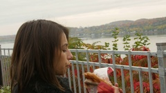 Woman eating beavertails in fall looking out towards water Stock Footage