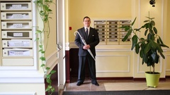 A man  with an umbrella stick stand near the front door and looking away Stock Footage
