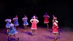 Girls in red and blue sarafans dancing on stage during concert Stock Footage
