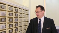 Man goes away and comes back into the hall with mailboxes. Stock Footage