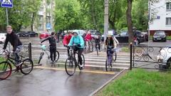 Cyclists cross the road at a pedestrian crossing on a rainy day Stock Footage
