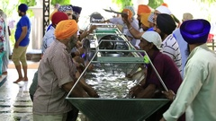 Poor people wash dishes at soup kitchen in Sikh Golden Temple, Amritsar, India Stock Footage