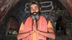 Indian sadhu , holy man, prays along the Ganges River.  Devprayag, India Stock Footage