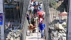People crossing Laxman Jhula footbridge on river Ganges , Rishikesh. India Stock Footage