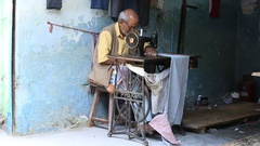 Street tailor working on a foot sewing machine , Devprayag . India Stock Footage