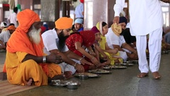 People eating free food at soup kitchen in Sikh Golden Temple, Amritsar, India Stock Footage