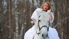 Beautiful girl in a white dress and a fur coat sits on a white horse Stock Footage