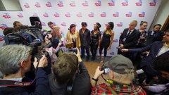 Group of journalists take interview of musicians near press wall Stock Footage