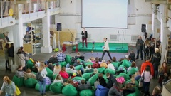 Many people sit at green bags and listen lecture during vegetables eaters Stock Footage