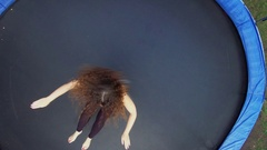 Woman in sports suit jumps on round trampoline. Aerial view Stock Footage
