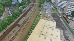 Parking for DHL company trucks near railroad at summer day. Aerial view Stock Footage