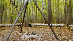 Chain swings on tripod above fire place in forest at autumn day Stock Footage