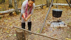 Woman chops stick near kettle under smolder fire place at autumn day Stock Footage
