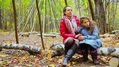 Mother and her daughter sit on birch trunk near carcase of wigwam Stock Footage